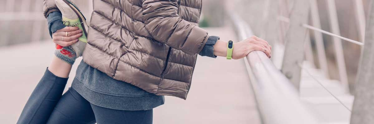 woman stretching for running in the city wearable watch for measure calories