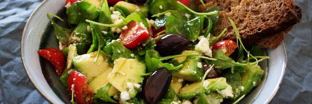 dish of avocado salad with arugula tomatoes black olives and bread